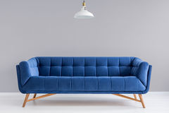 Grey interior with stylish upholstered sofa Royalty Free Stock Image