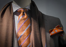 Grey jacket with brown scarf, orange tie and handk. Close-up of a grey jacket with brown scarf, white checkered shirt, orange striped tie and handkerchief royalty free stock image