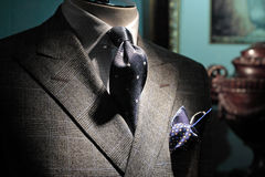 Grey jacket, dark blue tie and handkerchief. Close-up of a grey checkered jacket with white checkered shirt, dark blue tie and handkerchief stock images