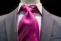 Grey jacket with magenta tie. Close-up of a grey jacket with white striped shirt and bright magenta tie on black background stock photos