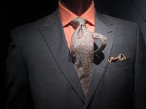 Grey jacket with orange shirt, tie and handkerchie. Close-up of a dark grey jacket with orange shirt, patterned tie and handkerchief stock photo