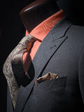 Grey jacket with orange shirt, tie & handkerchief. Close-up of a dark grey jacket with orange shirt, patterned tie and handkerchief royalty free stock photography