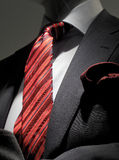 Grey jacket, red striped tie and handkerchief. Close-up of a dark grey striped jacket with white shirt, striped red tie and red handkerchief Stock Photo