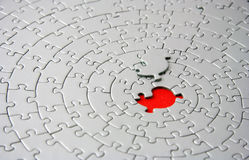 Grey jigsaw with the missing piece laying above the red space Royalty Free Stock Photography