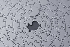 Grey jigsaw with the missing piece laying above the space. Shallow DOF, focus is on the hole - adobe RGB Stock Photography
