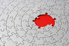 Grey jigsaw with missing pieces in the red center Royalty Free Stock Photography