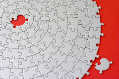 Grey jigsaw with one missing piece laying aside Royalty Free Stock Photo