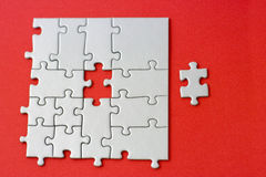 Grey jigsaw with one missing piece laying aside Royalty Free Stock Image