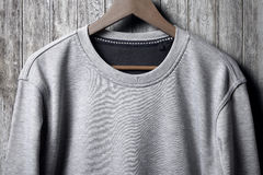 Grey jumper hanging on wood wall Royalty Free Stock Photo