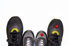 Grey kid sneakers with little red heart and pair of black adult sneakers stock image