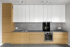 Grey kitchen with wooden cabinets. Granite worktop and white cupboards stock photos