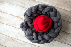 Grey knitted scarf of merino wool with a ball of red merino wool. Inside, on wooden floor royalty free stock photography