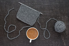 Grey knitting and coffee on black background Royalty Free Stock Photography