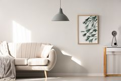 Grey lamp in bright living room interior with poster next to bei. Ge sofa. Real photo royalty free stock photo