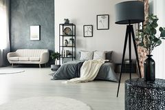 Grey lamp in multifunctional bedroom. Designer table and grey lamp in multifunctional bedroom with king-size bed and sofa against walls with posters stock image