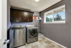 Grey laundry room with modern stainless steel appliances Royalty Free Stock Images