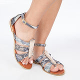 Grey leather sandals with gold applied on feet the mujere on white background Stock Images