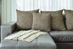 Grey leather sofa with texture brown pillows in living room Stock Photography