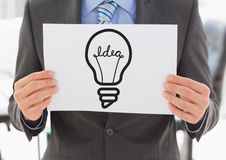 Grey lightbulb graphic on blank card held by business man mid section Stock Photo