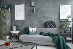 Grey living room with couch. Glass carafe on table in grey living room with green blanket on couch and white pillow on chair Royalty Free Stock Images