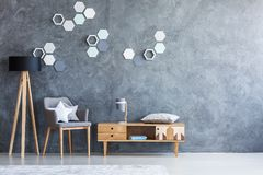 Grey living room with cupboard. Grey chair with star pillow between wooden lamp and vintage cupboard in living room interior with copy space on concrete wall stock photo