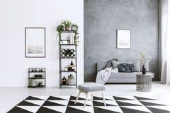 Grey living room. Interior with asymmetrical carpet, metal shelf, stool, and sofa stock photos