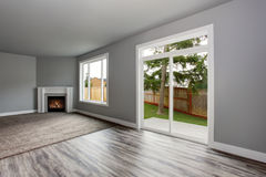 Grey living room interior.  Windows and Glass doors overlooking the back yard. Grey living room interior with fireplace. Windows and Glass doors overlooking the Stock Image