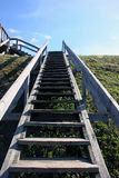Grey long wooden staircase with wooden railings on the green hil. L, view from the bottom up and blue sky Stock Photo