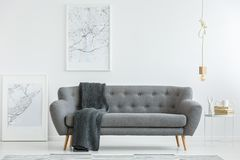 Grey lounge with blanket. Grey lounge with dark blanket standing in white living room interior with two map posters, gold bulb lamp and books on a small table stock image