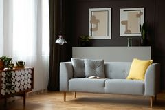 Grey lounge in real photo of dark living roo. Grey lounge with yellow cushion in real photo of dark living room interior with window with drapes, retro cupboard royalty free stock photo
