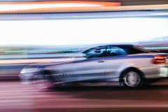 Grey Luxury Car in einer unscharfen Stadt-Szene lizenzfreie stockfotografie