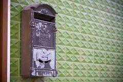 Grey Mailbox idoso em uma parede verde imagens de stock royalty free