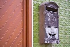 Grey Mailbox idoso em uma parede verde fotos de stock royalty free