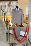 Grey man suit with blue tie and white shirt on mannequin. In the hall of hotel. Concept of vip tourist. Business suit for mens. Business style Stock Photography