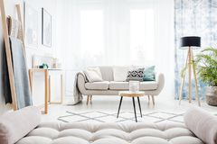 Grey mattress in daily room. Grey mattress, ladder and table in daily room with lamp next to a beige settee with pillows Stock Photo