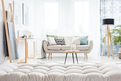 Grey mattress in living room. Grey mattress and ladder in bright living room with beige settee, table and lamp Stock Photos