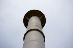 Grey metal pipe chimney against the gray sky. View from below Stock Photography