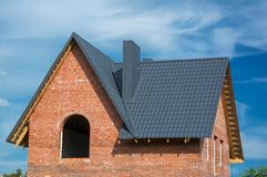 Grey metal tile roofing construction and Building New Brick House with Chimney. Over blue sky royalty free stock photos