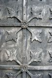 Grey metallic door of an old church. Decorated by floral ornament. Vertical background. No people Royalty Free Stock Photos