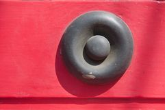 Grey metallic iron rivet on red wall background. Grey metallic iron bullet small rivet on red wall background Royalty Free Stock Photography