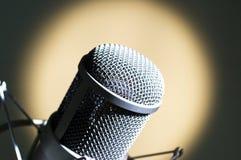 Grey microphone. Microphone in studio. Yellow light Stock Photo