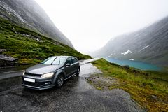 Grey modern car is parking next to a rural road in a valley surrounded by a fjord and snow covered mountains on a rainy day in Nor royalty free stock photography