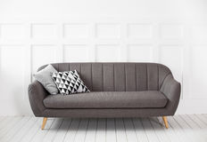 Grey modern sofa in a white room Stock Images