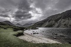 Grey, moody sky over scenic mountain valley with lake in Lake District,Cumbria,England. Grey and cloudy sky above majestic valley with lake and mountain peaks in royalty free stock photos