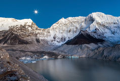 Grey moraine lake and snowy mountain peak in the. Stock Photography