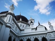 Grey mosque with blue sky. Grey mosque with black dome and clear blue sky royalty free stock photos