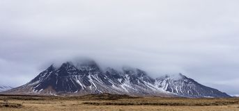 Grey Mountains Reaching Grey Clouds With Dirt Plains on Foot Stock Photography