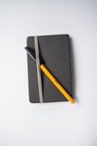 Grey notebook with a orange ballpen on it Royalty Free Stock Photos