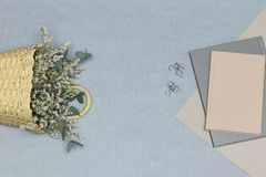 Grey notebook & paper clips, pink note & paper, straw basket with white flowers and eucalyptus branches stock photo