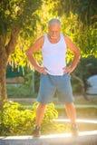 Grey Old Man in den Westen-Ständen lächelt gegen tropischen Baum lizenzfreies stockfoto